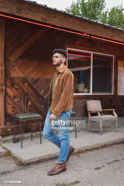 young man walking outside restaurant - one young man only stock pictures, royalty-free photos & images