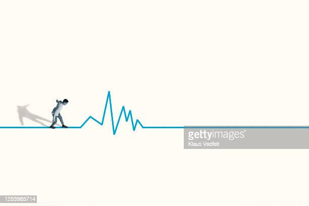 young man walking stealthily on blue line graph - information overload stock pictures, royalty-free photos & images