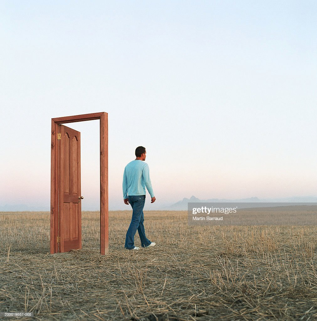 Young man walking through door in open landscape : Stock Photo