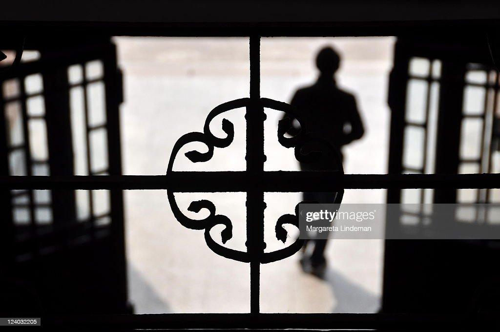 Young man walking through open door into light : Stock Photo