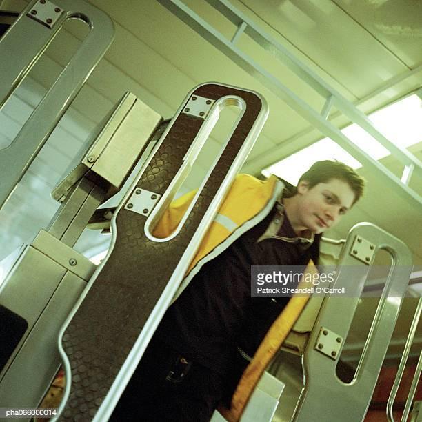 Young man walking through turnstile gate in subway.