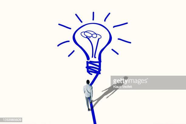 young man walking towards bright blue bulb - oplossing stockfoto's en -beelden