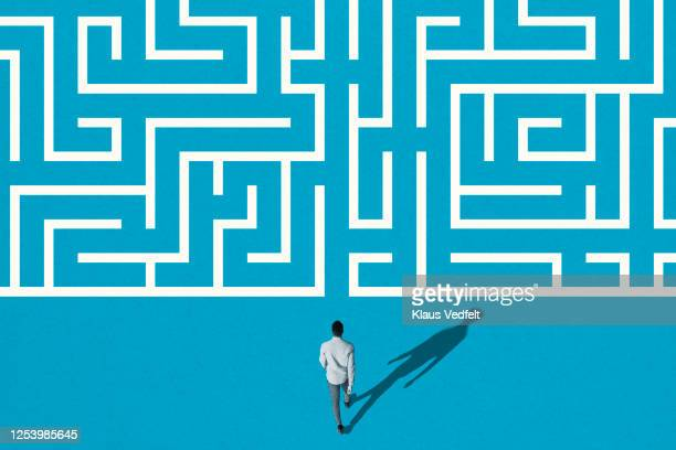 young man walking towards white maze pattern - beginnings stock pictures, royalty-free photos & images