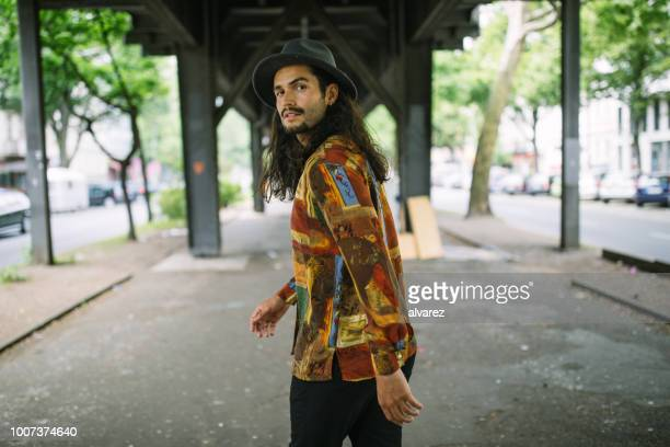 young man walking under the bridge in city - long hair stock pictures, royalty-free photos & images