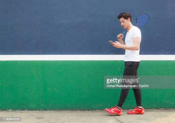 young man walking with badminton racket while using smart phone against wall - badminton sport stock pictures, royalty-free photos & images