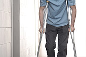 Young man walking with crutches