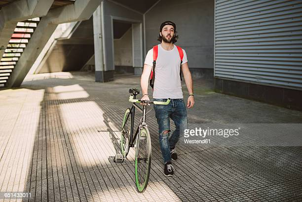 Young man walking with fixie bike