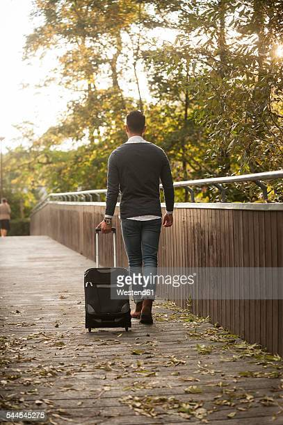 Young man walking with his wheeled luggage on a footbridge