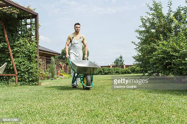 young man walking with wheelbarrow in backyard - wheelbarrow stock photos and pictures