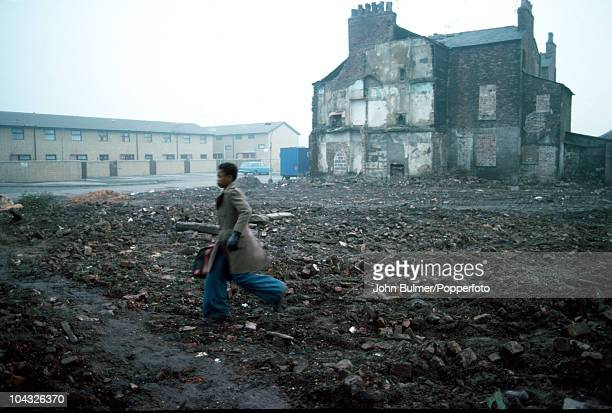 A young man walks across the rubblefilled Alexandra Park in Manchester England in 1976