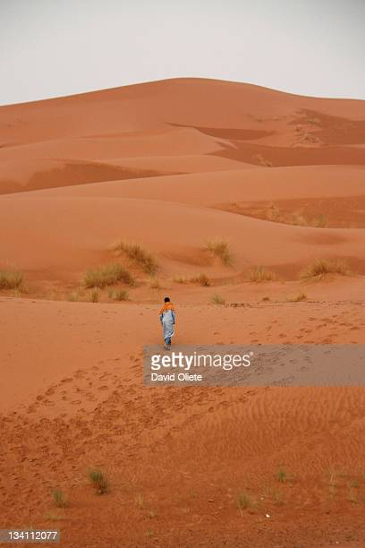 Young man walks alone in orange desert