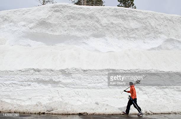 A young man walks along a snow bank in Lake Tahoe, California.