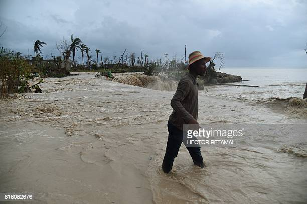 TOPSHOT A young man walks by the floodwaters of a river blocked by debris left by Hurricane Matthew in the commune of RocheaBateaux in the south west...