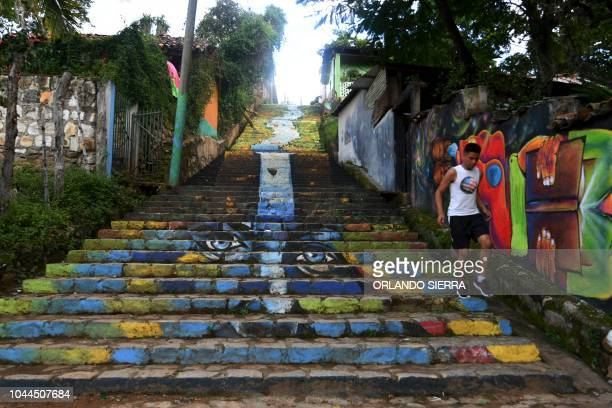 A young man walks down the steps next to murals in a street of Cantarranas municipality Francisco Morazan department 45 km west of Tegucigalpa on...
