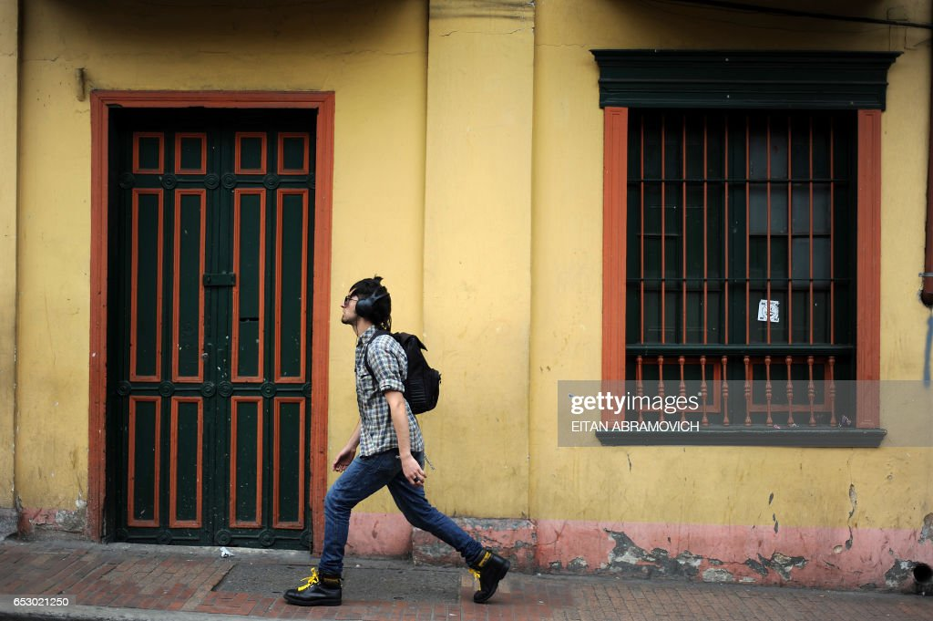 A young man walks down the street in the historic neighborhood of La Candelaria in Bogota on September 17, 2009. La Candelaria is Bogota's oldest neighbourhood and the city's historical center, known for its colonial houses with wooden balconies and clay shingle roofs. AFP PHOTO/Eitan Abramovich -------------- MORE