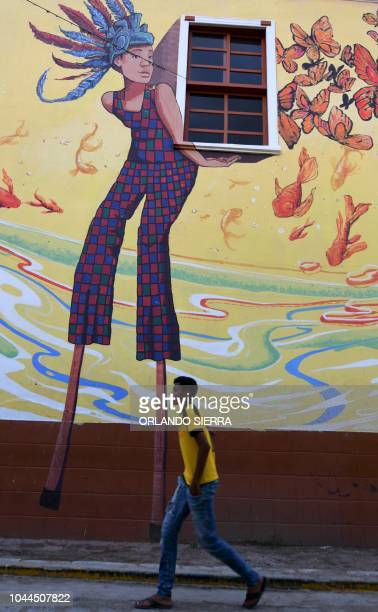 A young man walks past a mural in a street of Cantarranas municipality Francisco Morazan department 45 km west of Tegucigalpa on October 1 2018