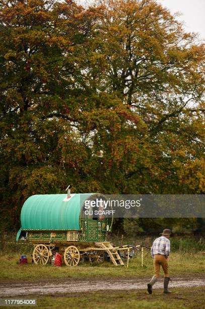 A young man walks past a traditional Gypsy caravan at the biannual Stow Horse Fair in the town of StowontheWold England on October 24 2019 The Stow...
