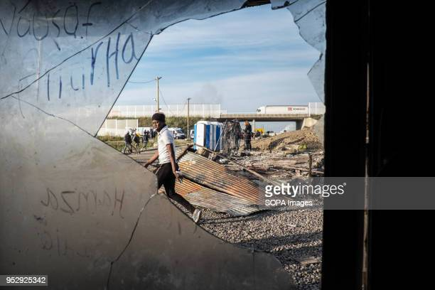 A young man walks past the burnt out ruins of a shop in the Jungle The Jungle was an illegal migrant camp in the northern French town of Calais The...