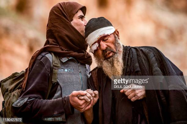 TOPSHOT A young man walks with an elderly one injured in his eye with others said to be members of the Islamic State group by the USbacked Syrian...