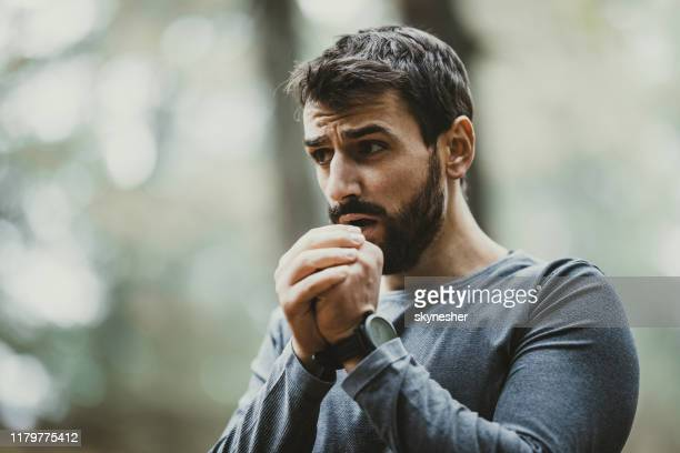 young man warming his hands during cold in nature. - shaking stock pictures, royalty-free photos & images