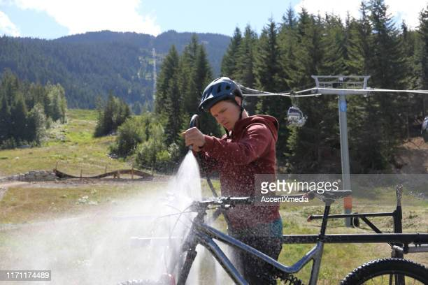 young man washes mountain bike, at bike park - red tube top stock photos and pictures