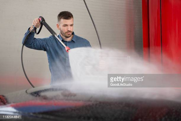 young man washing his car - high pressure cleaning stock pictures, royalty-free photos & images