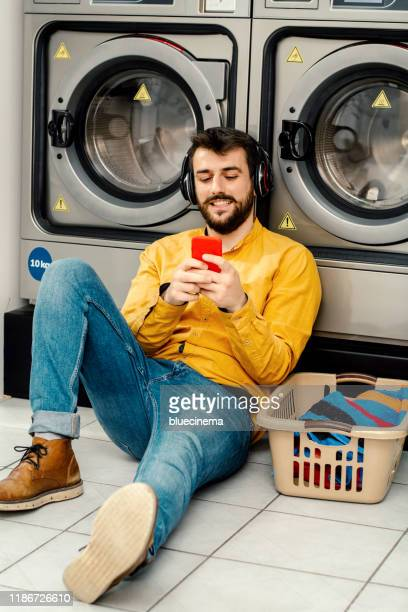 young man washing his clothes - launderette stock pictures, royalty-free photos & images