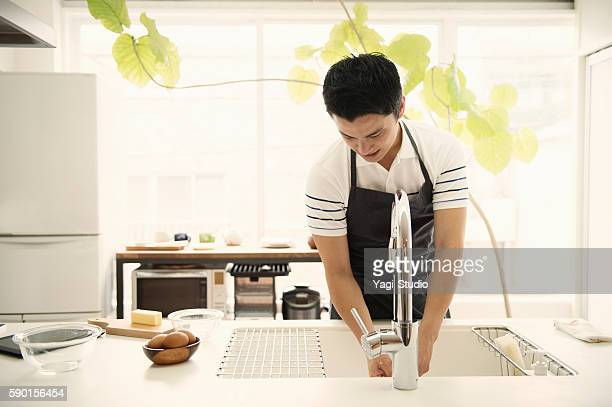 Young man washing the dishes in the kitchen