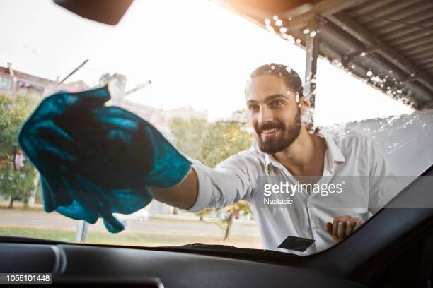 young man washing windshield - windshield stock pictures, royalty-free photos & images