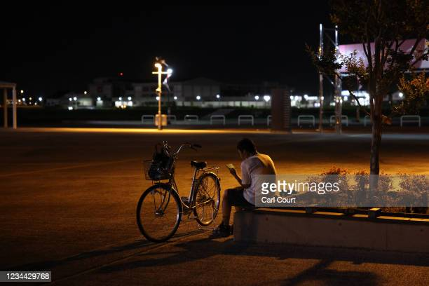 Young man watches Japans mens semi-final match against Spain on a smartphone outside Saitama Stadium where the game is being played without...