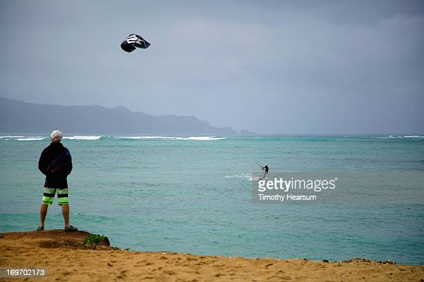 young man watches kite surfer on a cloudy day - timothy hearsum imagens e fotografias de stock