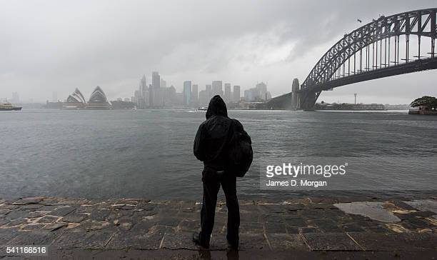 A young man watches pouring rain as he walks near the Harbour Bridge on June 19 2016 in Sydney Australia Flood warnings have been issued for the nine...