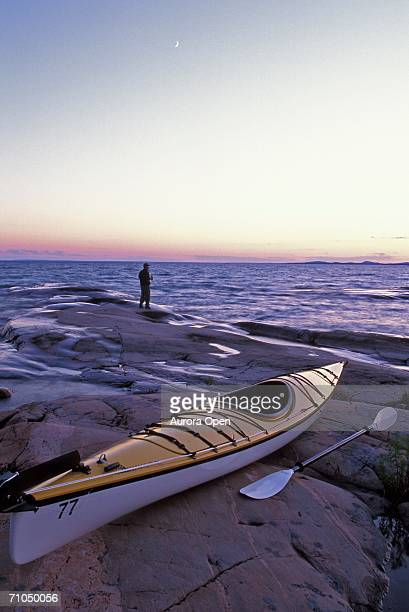 young man watches sunset with sea kayak on shore of georgian bay, lake huron, ontario, canada. - sudbury canada stock photos and pictures