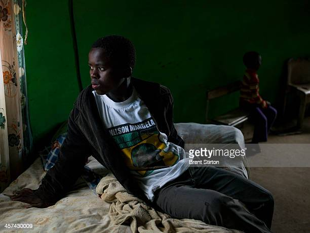 A young man watches through the window of his home as a crowd gathers on a hilltop for the Nelson Mandela funeral Qunu South Africa 14 December 2014...