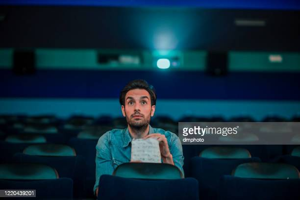 young man watching a movie - film screening stock pictures, royalty-free photos & images