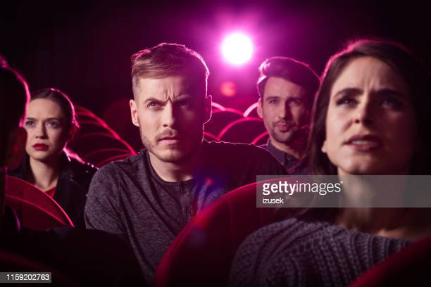 young man watching an interesting movie at the cinema - action movie stock pictures, royalty-free photos & images