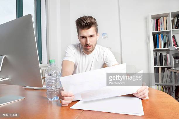 Young man watching documents at desk in an office
