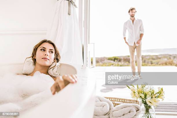 Young man watching girlfriend in bubble bath from patio door
