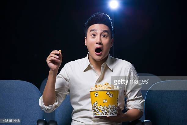 Young man watching horrible movie in cinema