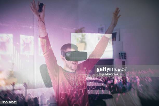 young man watching live concert on virtual reality simulator - live event stock pictures, royalty-free photos & images