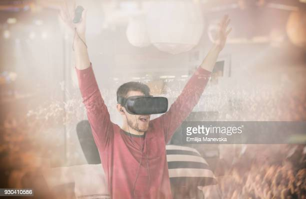 Young man watching live concert on virtual reality simulator