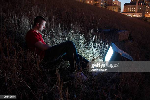 Young man watching television outside.