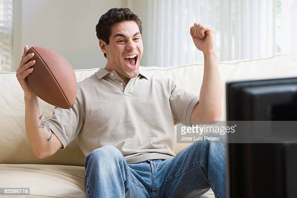 young man watching television with football in han - west new york new jersey stock pictures, royalty-free photos & images