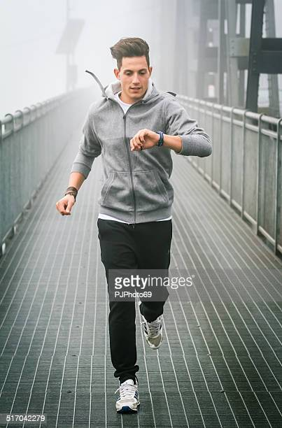 Young man watching the chronograph during running session