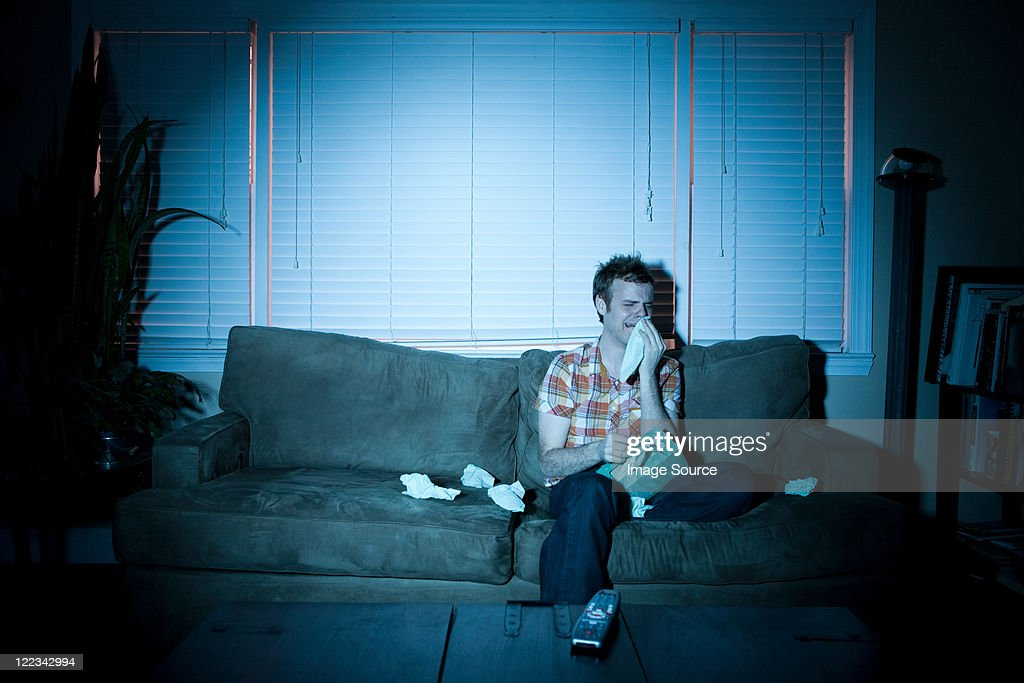 Young man watching tv, crying : Stock Photo