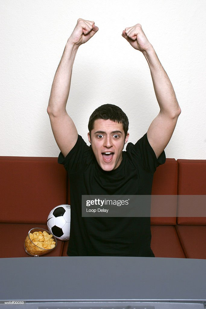 Young man watching TV, punching the air : Stock Photo