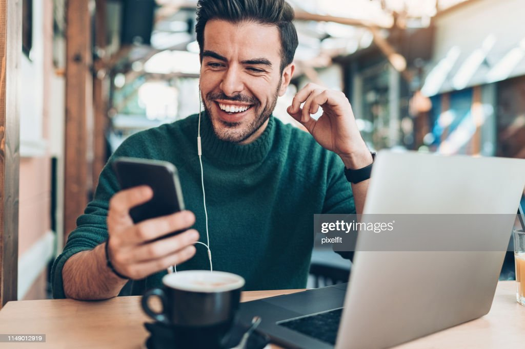 Young man watching video on his cell phone : Stock Photo