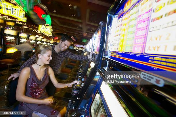 Young man watching young woman play casino fruit machine