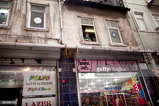 Young man watchs from his window together with a german shepherd dog on October 15, 2009 in the distirct Beyoglu in Istanbul, Turkey. The Turkish...