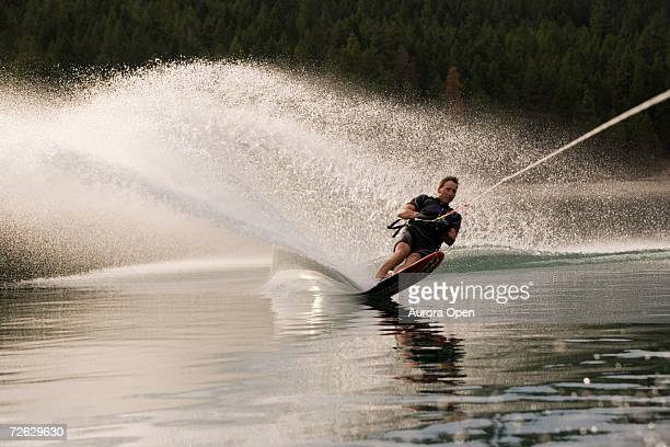 young man waterskiing on lake koocanusa in the east kootenays near fernie, british columbia, canada. - waterskiing stock photos and pictures